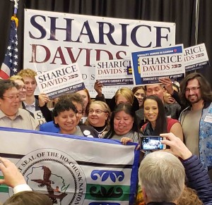 Sharice Davids celebrates her historic win with her mother Crystal Herriage and other Native Americans holding the Ho-Chunk tribal flag. Photo by Rhonda LeValdo